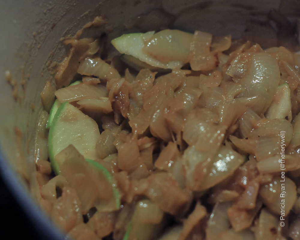 Add apple slices to onions and stir.